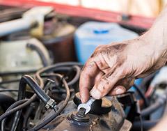 Egy olajos kéz, az autó motorján egy csavart húz meg.
