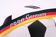 Egy focilabda, ami körül egy német zászló színű szalag van.
