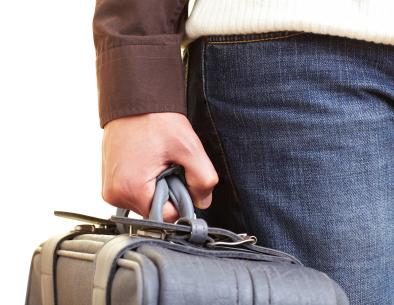 Egy férfi kéz akinek a kezében bőrönd van.