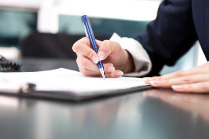 Egy férfi tollal kitölt egy papírt.