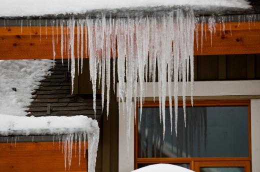 Egy ház aminek az ereszéről lógnak a jégcsapok.