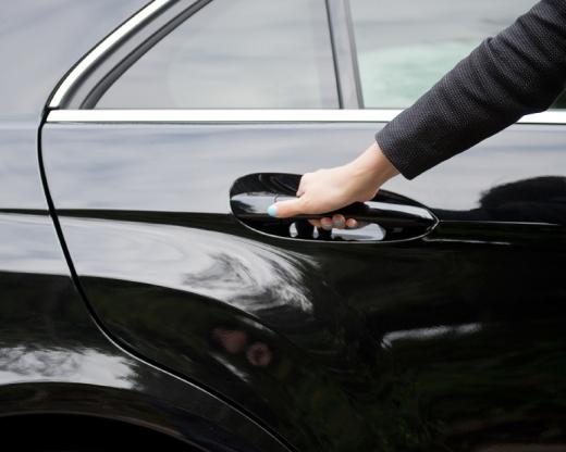 Egy női kéz kinyit egy fekete autó hátsó ajtaját.