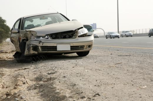 Egy autó az autópálya szélén, az eleje nagyon össze van törve.