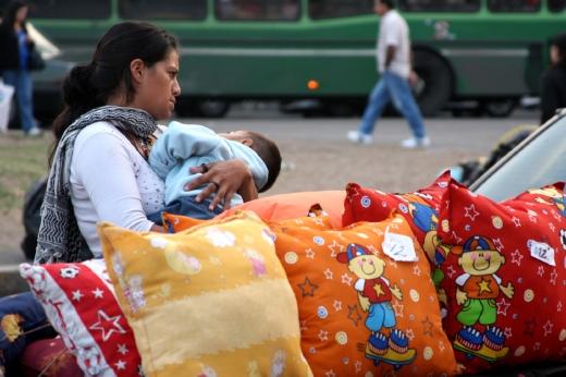 Egy menekült nő, ölében a gyereke, színes párnák mögött áll.