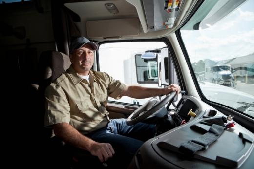 Egy kamionos ül a fülkében és keze a kormányon.
