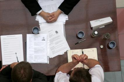 Három ember ül egy asztalnál papírokkal felülnézetben.