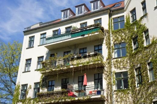 Egy több szintes ház, a falon és az erkélyen növény fut fel.