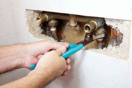 Egy vízszerelő a kibontott falban csövet szerel.