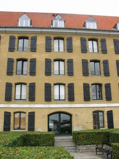 Egy 3 szintes barnás épület, minden ablaksötétítő nyitva.