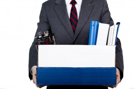 Egy öltönyös férfi kezében doboz amiben a munkahelyi dolgai vannak.