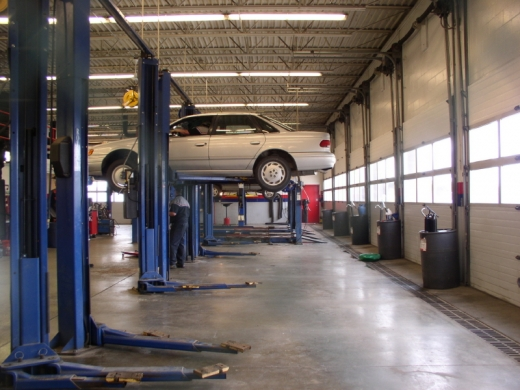 Egy autószerelő műhelyben egy autó fel van emelve és a szerelő alatta áll.