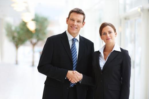 Egy öltönyös férfi és egy nő kezet fog.