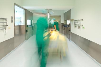 Egy kórházi folyosón két ápoló tolja a beteget, akik el vannak homályosítva.