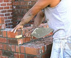 Egy kőműves falat rak.