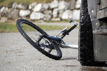 Egy kamion első kereke előtt egy felborult bicikli.