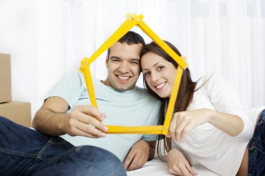 Egy fiatal pár félig fekve egy sárga mérőlécből házat mutat nekünk.