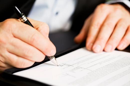 Egy férfi kéz aláír egy papírt.