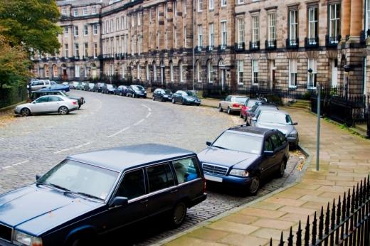 Egy kanyargós úton, a járda mellett végig parkoló autók.