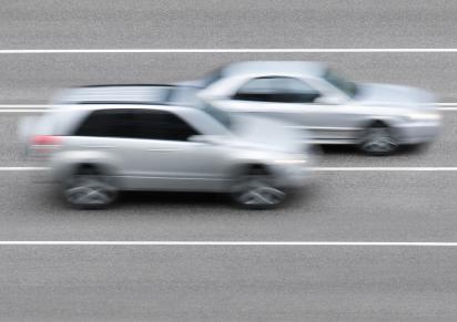 Az autópályán két autó elhomályosítva halad.