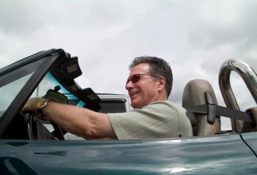 Egy férfi vidáman vezet egy kabrió autót.
