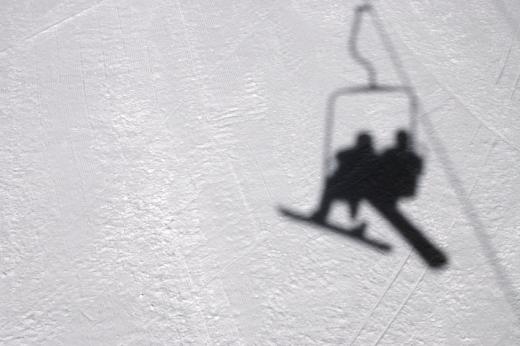 Egy sífelvonó árnyéka az alatta lévő hóban.