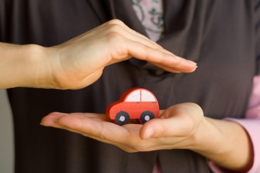 Egy nő kezében egy piros fa kisautó, a másik keze az autó fölött.