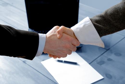 Egy papír és laptop felet két ember kezet fog.