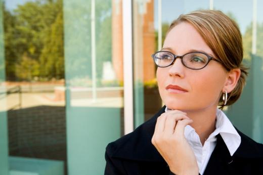 Egy szemüveges nő kezével állát támasztja és oldalra néz.