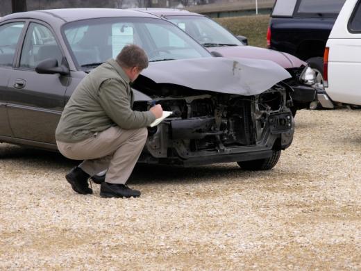 Egy férfi jegyzetel egy autó előtt guggolva, aminek az eleje leszakadt.