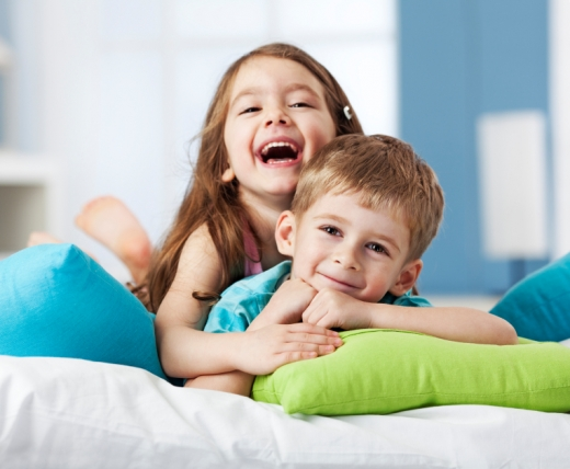 Egy kisfiú és egy kislány hason fekszik egy ágyon.