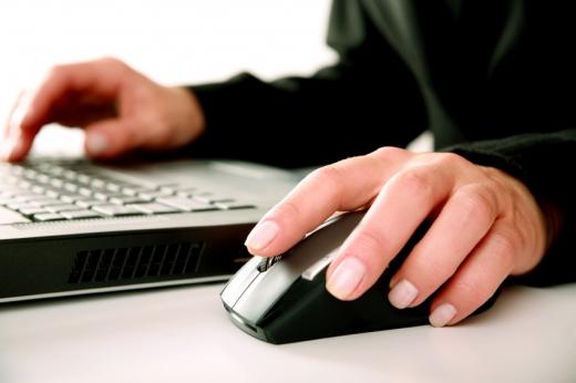 Egy kéz a laptopon, egy az egéren.