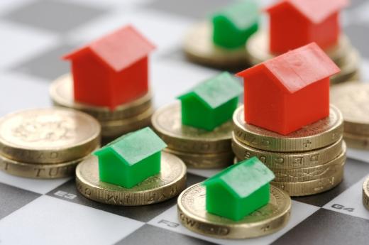 Aprópénzek több oszlopba egymásra rakva, a tetejükön műanyag piros és zöld házak.