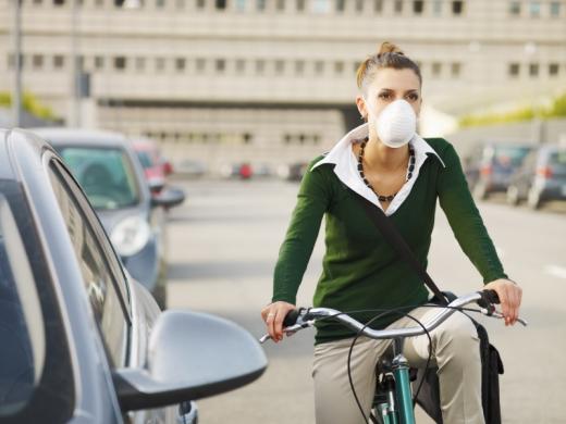 Egy nő az autók között biciklivel és számmaszkkal.