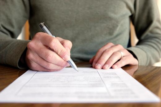 Egy kéz tollal nyomtatványt tölt ki.