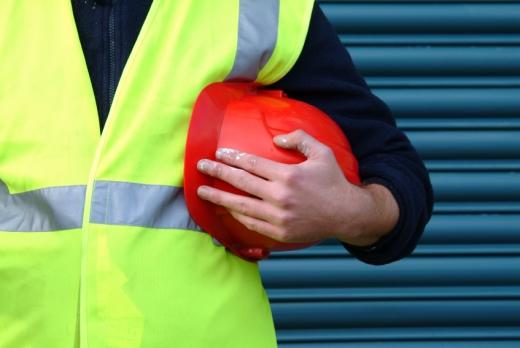 Egy építőmunkás hóna alatt egy piros sisakkal.