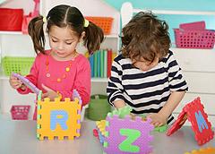 Két gyerek betűs szivacskockákat rak össze.