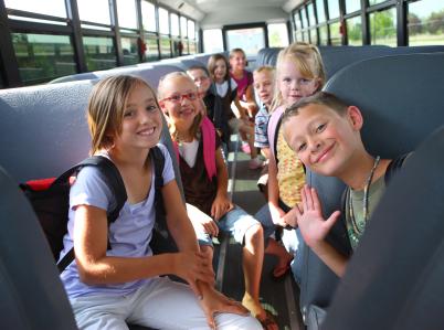 Egy buszon a gyerekek középre behajolva nevetnek és integetnek nekünk.