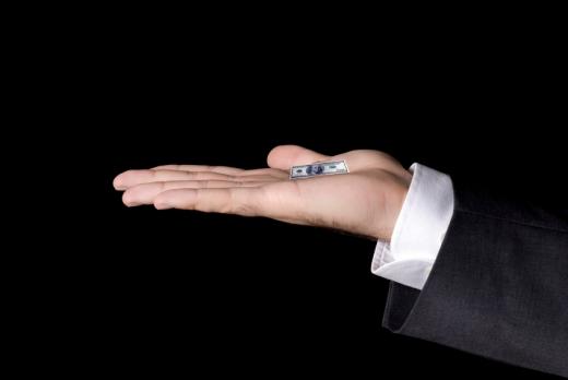 Egy kéz, vízszintesen nyitott tenyérrel, amiben egy lekicsinyített papírpénz van.