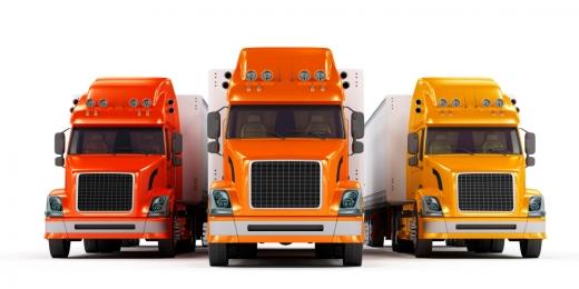 Egy piros, narancs és sárga kamion egymás mellett velünk szembe.