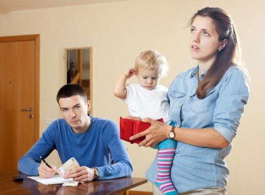 Apuka pénzzel és tollal a kezében ül az asztalnál, anyuka fogja a kezében a kisgyerekét és az üres pénztárcáját.