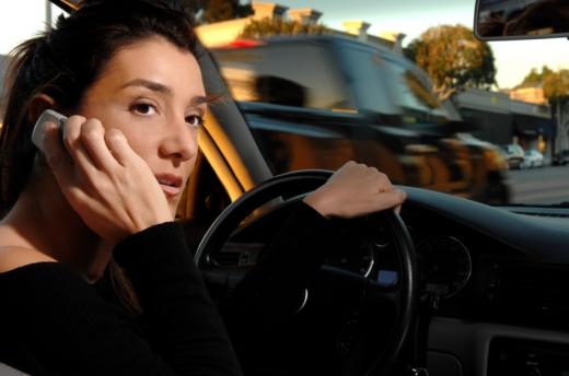 Egy nő vezetés közben telefonál és oldalra néz.