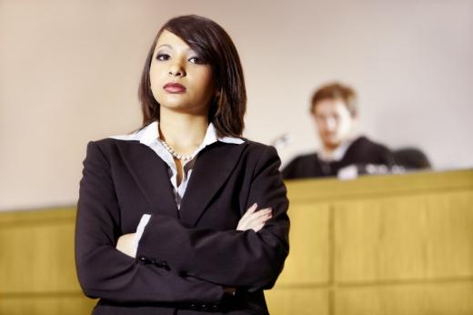 Egy elhomályosított bírói pulpitus előtt, karba tett kézzel áll egy nő.