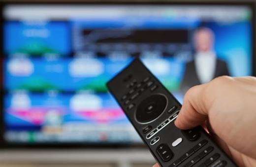 Egy kéz tart egy távirányítót, a háttérben homályosan egy tévé.
