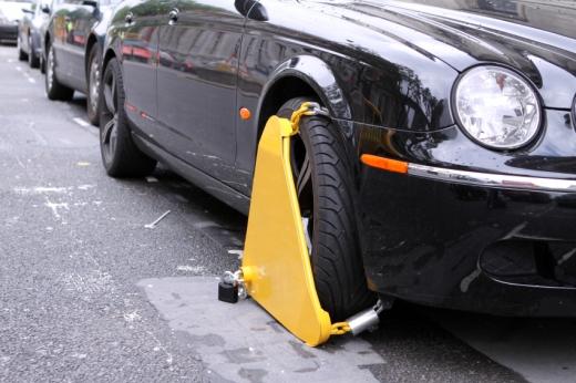 Egy autón sárga kerékbilincs.