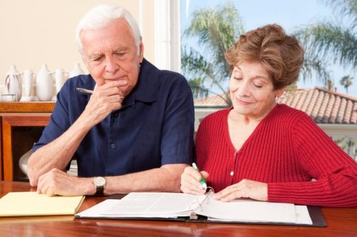 Egy idős pár az asztalnál egy mappában a papírjaikat nézik.