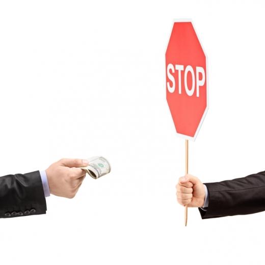 Egyik kéz pénzt adna a másiknak, de a másik stop táblát mutat.