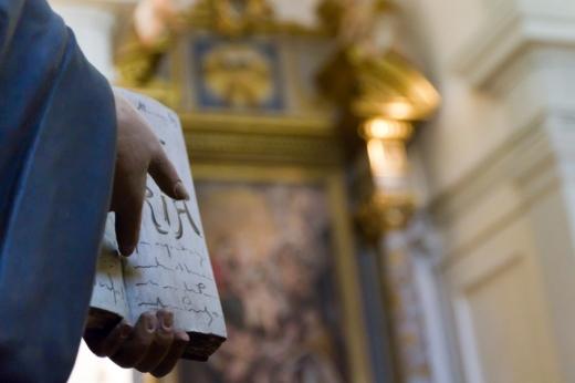Egy templomban egy szobor kezében egy könyv.