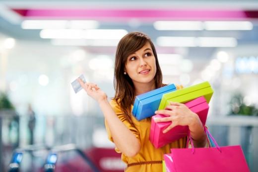 Egy nő kezében színes dobozokkal és szatyorral bevásárlás után bankkártyát felemeli.