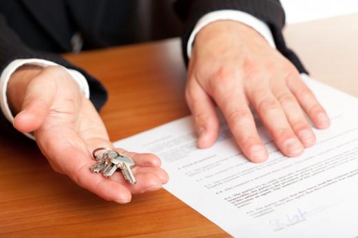 Egy férfi egyik kezében lakáskulcs, másik keze pedig egy papíron van az asztalon.