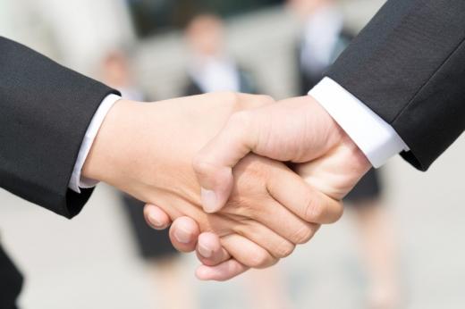 Két öltönyös ember keze, kezet fog.